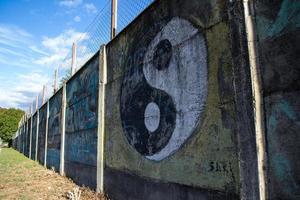 cementvägg med hög tråd - målad med yin yang symbol foto