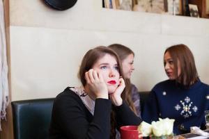 ung kvinna ignoreras av sina vänner i cafeterian foto