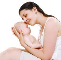 härlig lycklig mamma som håller på händer sin söta sovande baby foto
