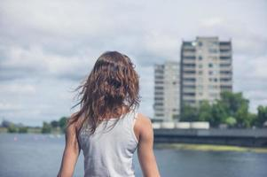 ung kvinna som står vid marinan i stadsområdet foto