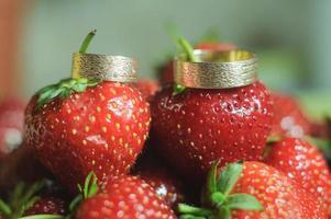 vackra vigselringar för brudgummen och bruden med jordgubbar foto