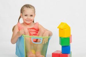 flicka klättrade i en låda för leksaker foto