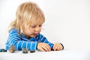 tre år gammal med plasticine foto