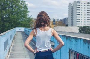 ung kvinna som står på en gångbro foto