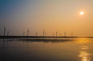 vindkraftverk vid solnedgången foto
