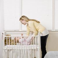 mamma sätter baby i spjälsäng foto