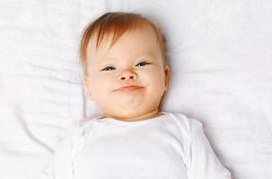 närbild porträtt söt positiv baby på sängen, ovanifrån foto