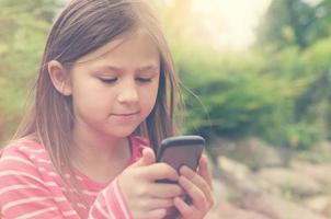 liten flicka och en smart telefon foto