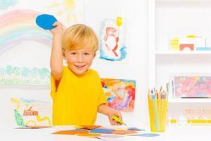 liten pojke med blont hår och pappcirkel foto