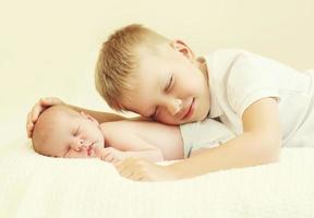 två barn som ligger på sängen hemma foto