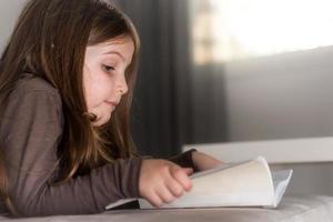 söt brun hårflicka som läser en bok hemma
