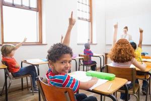 elev som lyfter upp sina händer under lektionen foto