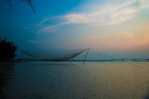lugn scen med fisknät mot lila solnedgång.
