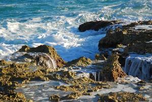 vågor på klipporna vid punta sur foto