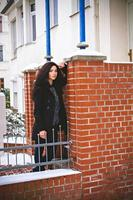 vacker kvinna nära orange tegelvägg foto