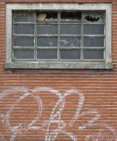 fasad på övergivna byggnader med trasiga fönster och graffiti