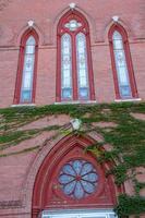 utsmyckade fönster i fasad av rött tegel, kyrka, keene, new hampshire. foto