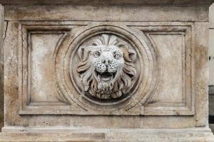lejonhuvud snidas i stenbyggnadsfasad foto