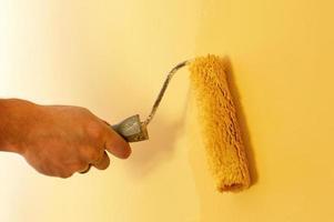 processen att måla väggarna i gul färg foto