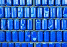 vägg av blåmålade använda metallburkar bakgrund foto