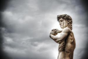 michelangelos david under en mulen himmel foto