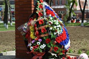 de lagt blommorna till monumentet för att hedra foto