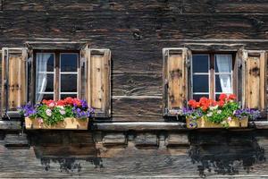 äldre fönster med blommor från en schweizisk alpin gård foto