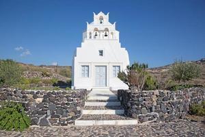 santorini - lilla kapellet över öns sydkust. foto