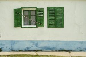 öppnade och stängde gröna fönster på vitt tappninghus foto