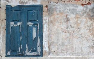 gammal husvit vägg med blått fönster foto