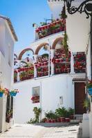 pittoreska gata av mijas med blomkrukor i fasader. andalus foto