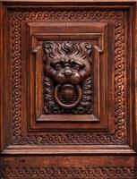 lejonhuvud som träsnideri i gammal dörr foto