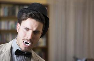 nära upp ung stilig vampyr med svart hatt foto