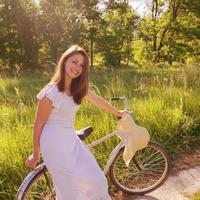 kvinna som går med en cykel foto