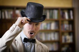 närbild ung vampyr med svart hatt foto