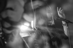 flicka sjunger in i en mikrofon i en studio foto