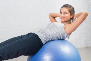 sport kvinna gör fitnessövning, sträcker sig på bollen. pilates foto
