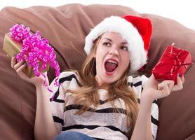 flicka sitter på stol med en gåva i händerna foto