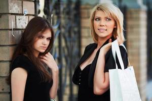 två unga kvinnor som går på en stadsgata foto