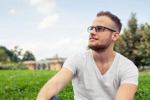 porträtt av skäggig ung man som ler glad i parken.