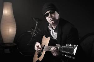man spelar gitarr foto