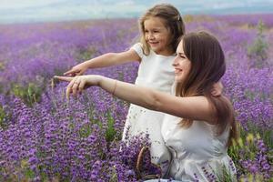 mamma med dotter i lavendelfält håller korg foto