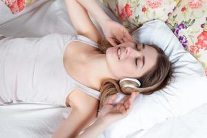 den unga flickan i sängen lyssnar på musik hörlurar foto