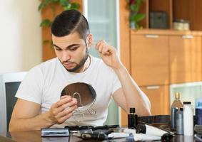 man plockar hår från näsan med en tång foto