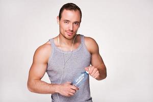 ung sportig man med en flaska vatten foto