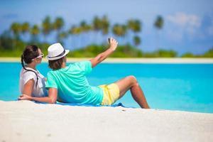 unga lyckliga par som gör selfie med mobiltelefonen på stranden foto