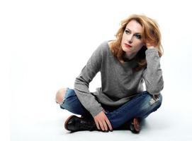 vacker blond kvinna sitter på golvet foto
