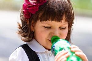liten flicka som dricker vatten från flaskan foto