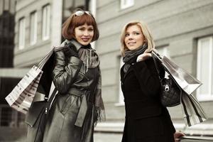 två unga modekvinnor med påsar foto
