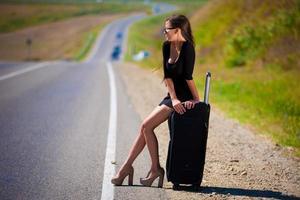brunett kvinna väg resväska foto